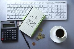Job text on notepad with stationary on keyboard royalty free stock images