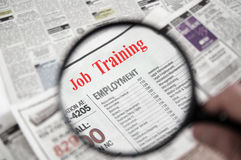 Job Training. Magnifying glass over a newspaper classified section with Job Training text royalty free stock image