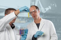 Job for two. Two Chemist colleagues are appraising a yellow liquid stock image