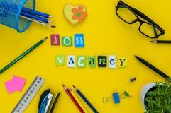 Job Vacancy-Aufschrift von geschnitzten Buchstaben auf gelbem Arbeitsplatz mit Büroartikel stockbilder