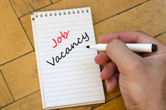 Job vacancy text concept. White notepad and human hand on the wooden background Stock Images