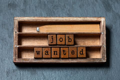 Job wanted phrase. Recruiting and work searching conceptual quote. Vintage box, wooden cubes with old style letters Royalty Free Stock Photography