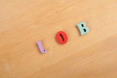 JOB word on wooden background composed from colorful abc alphabet block wooden letters, copy space for ad text. Learning Stock Images