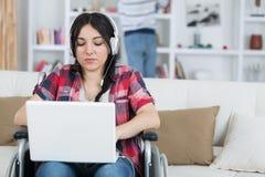 Jobb för kvinna för rörelsehindrat folk på rullstolen med bärbara datorn arkivbild