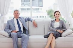 Jobbarkompisar som poserar tillsammans att sitta på soffan Royaltyfria Foton