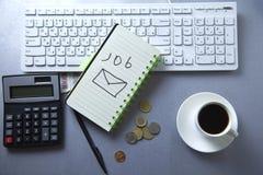 Jobbtext på notepaden med stationärt på tangentbordet royaltyfria bilder
