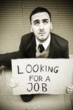 Jobless man. Young businessman holding sign Looking for a job Royalty Free Stock Image