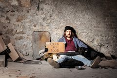 Jobless man with dog sitting on the city sidewalk. Portrait of jobless man with his dog sitting on the floor, holding keyboard and cardboard Code for food sign royalty free stock photography