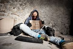 Jobless man sitting on city sidewalk with his dog. Jobless man sitting on the pedestrian footpath with his dog and holding cardboard Code for food sign royalty free stock photo