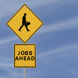 Jobs Ahead. Road sign with a silhouette of walking man (on a blue sky background with copy space royalty free stock photo