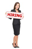 Jobs - businesswoman hiring. Hiring job woman holding hiring sign. Young attractive smiling Caucasian / Asian businesswoman isolated on white background Stock Photos