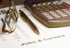 Jobs and careers. With a calculato, ballpoint pen and pair of reading glasses stock photo
