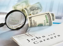 Jobs and careers. Image of selective focus shot of magnifying glass hundred dollars bills and Jobs and careers written on financial documents royalty free stock photography