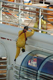 Jobs offered by the cruise ship and marine industries. Man in yellow uniform performing painting and maintenance of large cruise ship Royalty Free Stock Photo