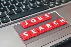 Jobs searching. Words made by red letter on a laptop palm royalty free stock photos