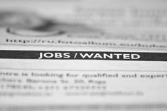 Jobs/Wanted. Words Jobs / Wanted focused in newspaper. Other text is blurred Royalty Free Stock Photo