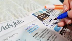 Jobzeichen unter dem Vergr??erungsglas auf einem wei?en Hintergrund lizenzfreie stockfotografie