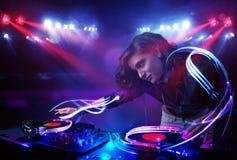 Jockey δίσκων παίζοντας μουσική κοριτσιών με τα αποτελέσματα ελαφριών ακτίνων στη σκηνή Στοκ Φωτογραφίες