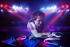 Jockey δίσκων παίζοντας μουσική με τα αποτελέσματα ελαφριών ακτίνων στη σκηνή Στοκ Φωτογραφία