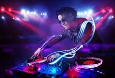 Jockey δίσκων παίζοντας μουσική με τα αποτελέσματα ελαφριών ακτίνων στη σκηνή Στοκ Εικόνες