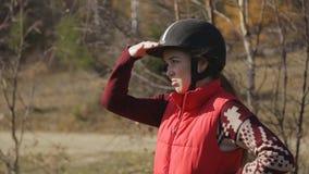 Jockey γυναικών στέκεται και εξετάζει την απόσταση που κρατά το χέρι ως γείσο και που ελέγχει την κατάσταση απόθεμα βίντεο