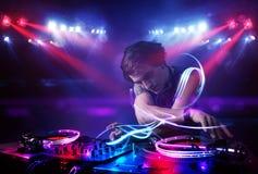 Jockey δίσκων παίζοντας μουσική με τα αποτελέσματα ελαφριών ακτίνων στη σκηνή Στοκ Εικόνα