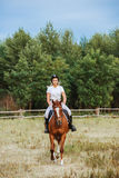 Jockey κοριτσιών που οδηγά ένα άλογο Στοκ Φωτογραφίες