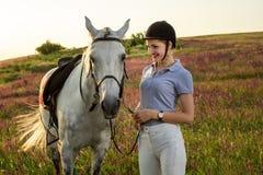 Jockey νέο κορίτσι που και που αγκαλιάζει το άσπρο άλογο στο ηλιοβασίλεμα βραδιού Στοκ Φωτογραφία