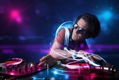 Jockey de disque jouant la musique avec d'électro effets de la lumière et lumières Photo stock