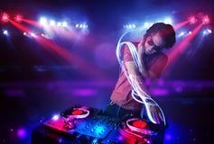 Jockey de disque jouant la musique avec des effets de faisceau lumineux sur l'étape illustration stock