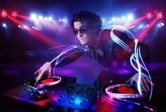 Jockey de disque jouant la musique avec des effets de faisceau lumineux sur l'étape Images stock