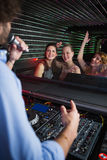 Jockey de disque masculin jouant la musique avec trois femmes dansant sur la piste de danse Images stock