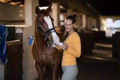 Jockey féminin à l'aide du téléphone intelligent tout en se tenant prêt le cheval photographie stock libre de droits