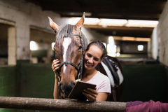 Jockey féminin de sourire à l'aide du comprimé numérique tout en se tenant prêt le cheval photos stock