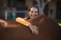 Jockey féminin de sourire se penchant sur le cheval à la grange Image libre de droits