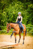 Jockey girl doing horse riding on countryside meadow. Taking care of animals, horsemanship, western competitions concept. Jockey girl doing horse riding on stock images