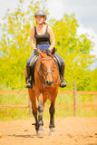Jockey girl doing horse riding on countryside meadow. Taking care of animals, horsemanship, western competitions concept. Jockey girl doing horse riding on stock photos