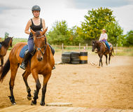 Jockey girl doing horse riding on countryside meadow. Taking care of animals, horsemanship, western competitions concept. Jockey girl doing horse riding on royalty free stock photography