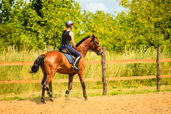 Jockey girl doing horse riding on countryside meadow. Taking care of animals, horsemanship, western competitions concept. Jockey girl doing horse riding on royalty free stock images