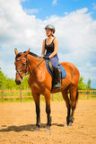 Jockey girl doing horse riding on countryside meadow. Taking care of animals, horsemanship, western competitions concept. Jockey girl doing horse riding on stock photography