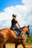 Jockey girl doing horse riding on countryside meadow. Taking care of animals, horsemanship, western competitions concept. Jockey girl doing horse riding on stock image
