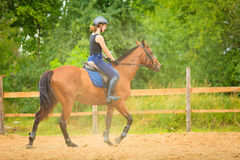 Jockey girl doing horse riding on countryside meadow Stock Photography