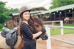 Jockey girl and her horse. Smiling jockey girl stroking her horse Stock Photos