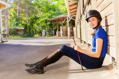 Jockey girl sitting outside a box stall with whip. Portrait of beautiful young woman wearing jockey outfit, sitting on the floor outside a box stall and holding Royalty Free Stock Photo