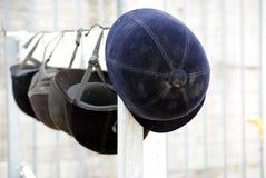 Jockey helmet. Row of jockey helmets on fence Stock Image