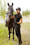 Jockey with horse. Image of happy female jockey with purebred horse outdoors Royalty Free Stock Photo