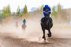 Jockey on a horse racing on race track Royalty Free Stock Photography