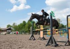 Jockey jumps over a hurdle Stock Images