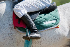 Jockey leg closeup sitting on racing horse Stock Photos