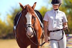 Jockey with purebred horse. Image of female jockey with purebred horse outdoors stock photography